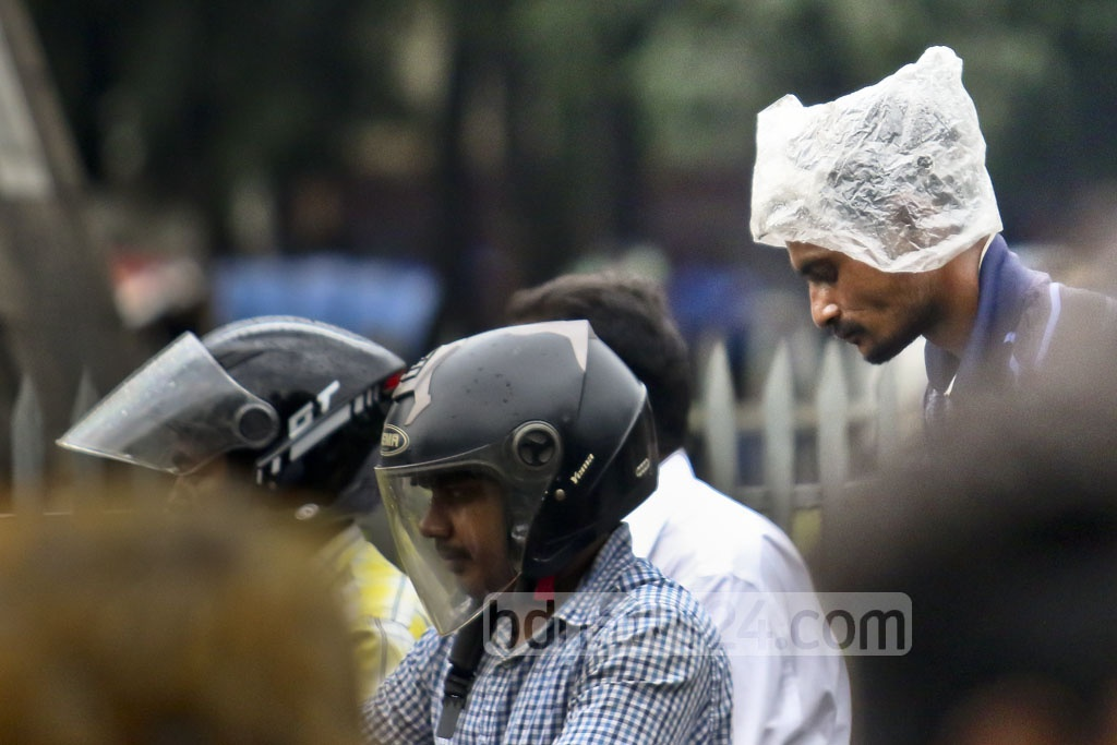 Riders of rickshaw in Dhaka use polythene sheets to cover themselves from drizzle on Thursday in Dhaka University area. Photo: dipu malakar