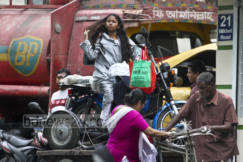 A girl and her mother are returning home with their new motorcycle on a rickshaw van. The photo is taken in Daka's Nilkhet on Thursday. Photo: dipu malakar
