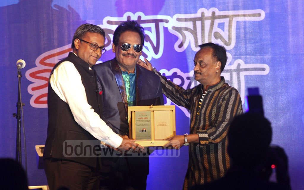 Music composer Alauddin Ali handing over a crest to singer Ferdous Wahid at a reception titled 'Gane Gane Gunijan Sangbardhana' arranged by Citi Bank NA at hotel Radisson in Dhaka on Friday. Photo: dipu malakar