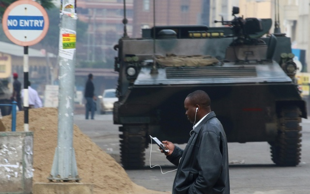 A man uses a mobile phone as he crosses the street in Harare, Zimbabwe Nov 17, 2017. Reuters