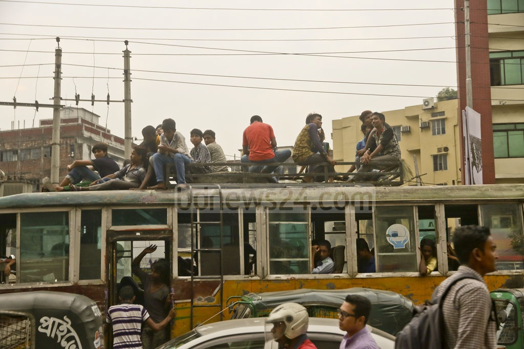Commuters take a ride on the rooftop of a bus by risking their lives. The photo is taken around 4:30pm on Saturday at Farmgate in the capital. Photo: tanvir ahammed