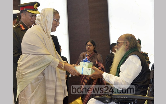 Prime Minister Sheikh Hasina hands commendations to decorated freedom fighters and their heirs at an Armed Forces Day reception at Army Multipurpose Complex in Dhaka Cantonment on Monday. Photo: PID