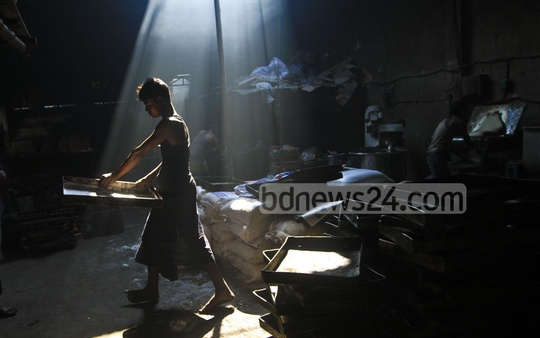 A teenaged boy working at a biscuit factory at Jinjira in Keraniganj. Photo: dipu malakar