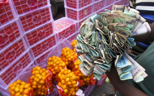 A trader holds a wad of cash in hand at the wholesale fruits market in Dhaka's Badamtali on Wednesday. Photo: dipu malakar
