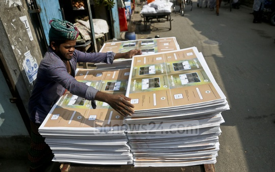 A worker carries textbook covers at Banglabazar in Old Dhaka on Thursday. Photo: tanvir ahammed