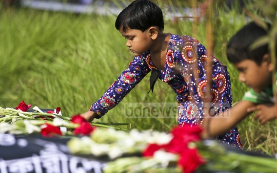 Children are placing flowers at Jurain graveyard on Friday on the fifth anniversary of Tazreen Fashions garment factory tragedy. Over 100 workers were killed in one of the worst factory fires in the country. Photo: dipu malakar