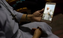 A Catholic nun from Kachin state show a picture of Pope Francis on her mobile phone while traveling on a two-day train trip from Myitkyina to Yangon to attend the pope's visit to Myanmar next week, November 23, 2017. Reuters
