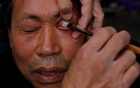 A customer looks on as Xiong Gaowu, a 62-year old street barber cleans his eye using the straight razor in Chengdu, Sichuan province, China November 18, 2017. Reuters