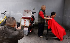 Xiong Gaowu (C), a 62-year old street barber talks to customer in Chengdu, Sichuan province, China November 18, 2017. Reuters