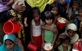 Rohingya women and children wait to get distributed meals at Moynarghona refugee settlement near Cox's Bazar, Bangladesh, Nov 24, 2017. Reuters