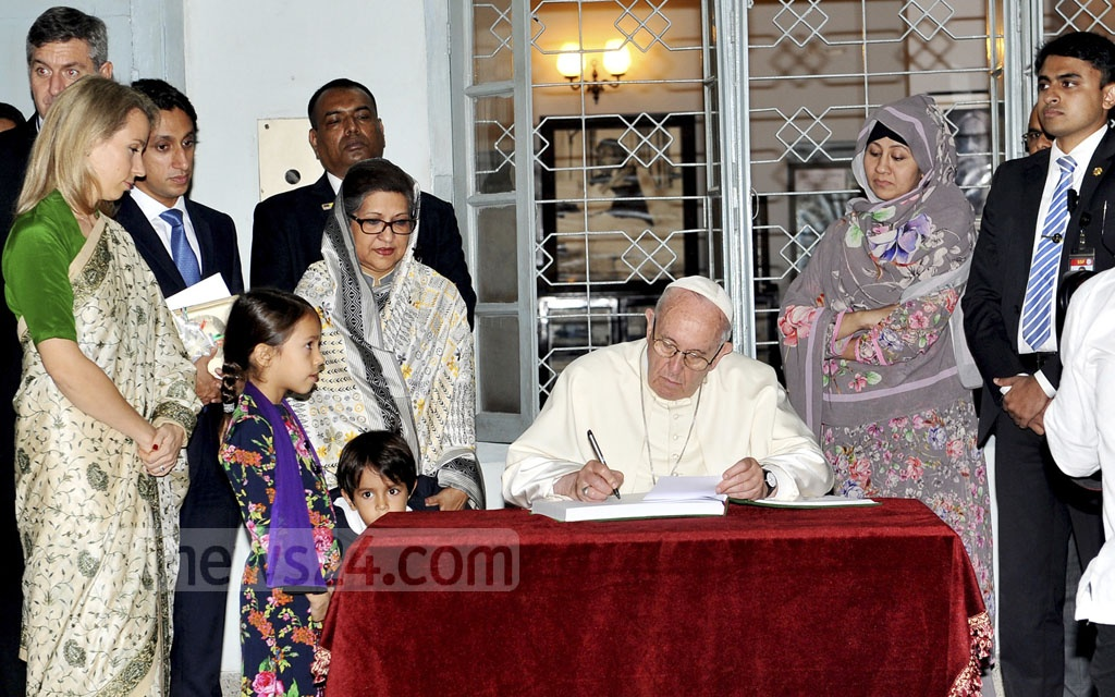 Pope Francis signs the visitors' book at the Bangabandhu Memorial Museum on Thursday. Photo: PID