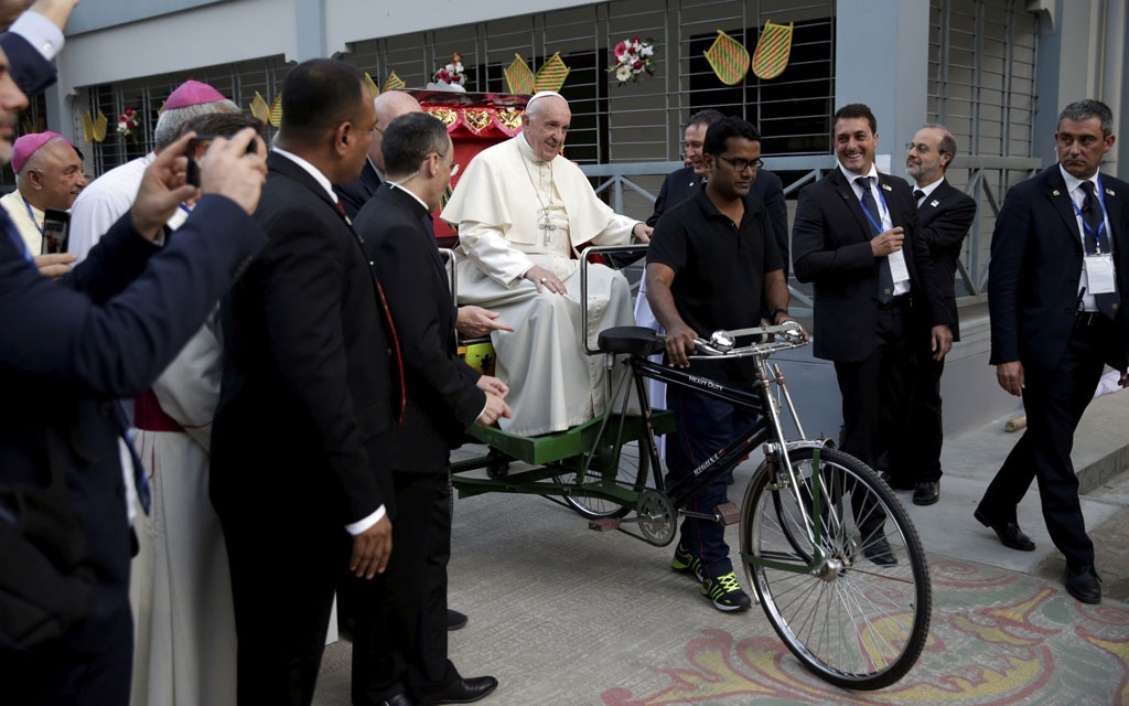 Pope Francis waves to the people in Dhaka as he takes a rickshaw ride at St Mary's Cathedral in Kakrail on Friday afternoon. Photo: Reuters