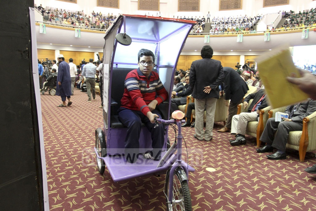 A group of physically-challenged people and wounded freedom fighters are given electric wheelchair on the International Day of Persons with Disabilities at a programme at the Bangabandhu International Conference Centre in Dhaka on Sunday. Photo: asif mahmud ove