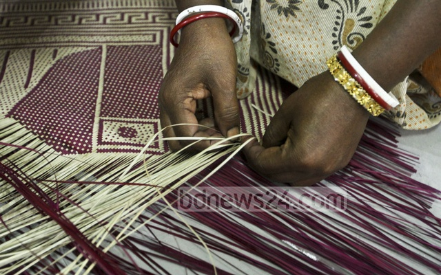 A craftswoman gives a live demonstration how to make Shital Pati (a traditional mat made of materials from murta plants) at the three-day exhibition opened at the National Museum at Shahbagh in Dhaka on Tuesday. Photo: dipu malakar
