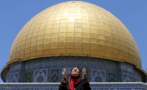 FILE PHOTO: A Palestinian woman prays in front of the Dome of the Rock on the first Friday of the holy month of Ramadan at the compound known to Muslims as the Noble Sanctuary and to Jews as Temple Mount, in Jerusalem's Old City June 19, 2015. Reuters