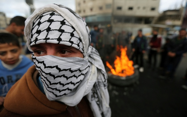A masked Palestinian takes part in a protest against US President Donald Trump's decision to recognize Jerusalem as the capital of Israel, in Khan Younis in the southern Gaza Strip Dec 7, 2017. Reuters