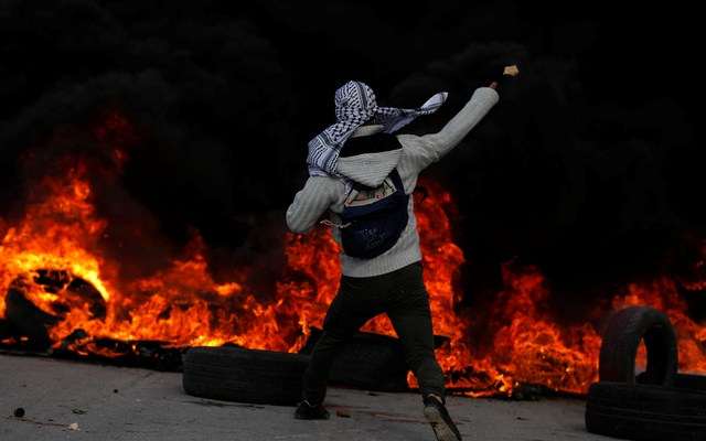 A Palestinian protester hurls stones towards Israeli troops during clashes at a protest against US President Donald Trump's decision to recognise Jerusalem as the capital of Israel, near the Jewish settlement of Beit El, near the West Bank city of Ramallah Dec 7, 2017. Reuters