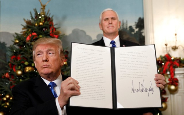 US Vice President Mike Pence stands behind as US President Donald Trump holds up the proclamation he signed that the United States recognizes Jerusalem as the capital of Israel and will move its embassy there, during an address from the White House in Washington, US, December 6, 2017. Reuters