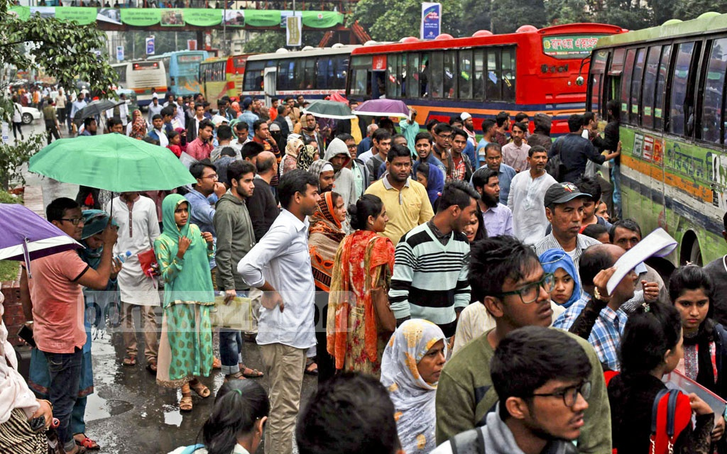 People wait for transports amid drizzle at Shahbagh in Dhaka on Saturday as a deep depression brings in rain in the capital and many other parts of the country.