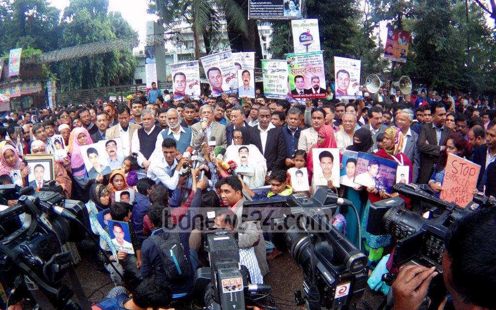 Relatives carry photos of victims of enforced disappearance at a human-chain programme of the BNP in front of the National Press Club in Dhaka on Human Rights Day on Sunday.