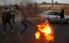 A Palestinian kicks a burning tire during clashes with Israeli troops at a protest against U.S. President Donald Trump's decision to recognize Jerusalem as Israel's capital, near the Jewish settlement of Beit El, near the West Bank city of Ramallah December 10, 2017. Reuters