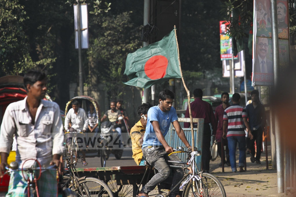 The Bangladesh flag seen on a rickshaw van in capital Dhaka on Friday. On Saturday, the country will celebrate 46 years of winning the 1971 Liberation War which ended on Dec 16 with the Pakistan Army's surrender at the then Ramna race course, now the Suhrawardy Udyan. Photo: dipu malakar