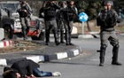 A Palestinian man with a knife and what looks like an explosive belt lies on the ground after being shot by Israeli border policemen near the Jewish settlement of Beit El, near the West Bank city of Ramallah December 15, 2017. Reuters