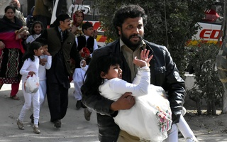 A man carries a girl as he runs out with others after gunmen attacked the Bethel Memorial Methodist Church in Quetta, Pakistan, Dec 17, 2017. Reuters