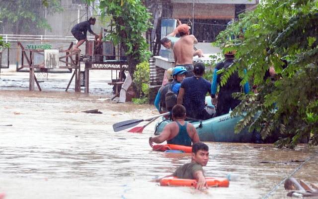 Police wade through Philippines flood waters coming to aid of young boy