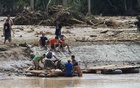 A man and his motorcycle are transported on a makeshift raft, after a bridge was destroyed by flash floods in Salvador, Lanao del Norte in southern Philippines, Decr 23, 2017. Reuters