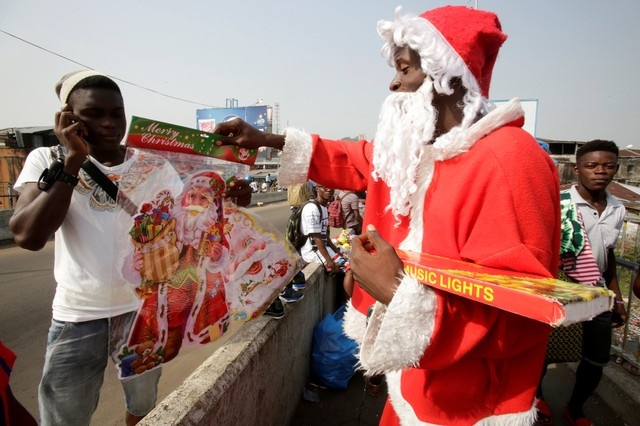 A man dressed as Santa Claus sells Christmas decorative objects at West point in Monrovia Liberia, December 23, 2017. Picture taken on December 23, 2017. REUTERS