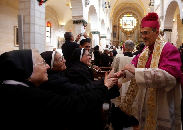 The Latin Patriarch of Jerusalem Pierbattista Pizzaballa is greeted as he arrives at the Church of the Nativity in the West Bank city of Bethlehem December 24, 2017. REUTERS