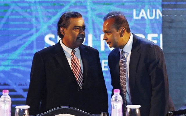 FILE PHOTO: Anil Ambani (R), chairman of the Reliance Anil Dhirubhai Ambani Group, talks to his brother Mukesh Ambani, chairman of Reliance Industries Limited, during the launch of