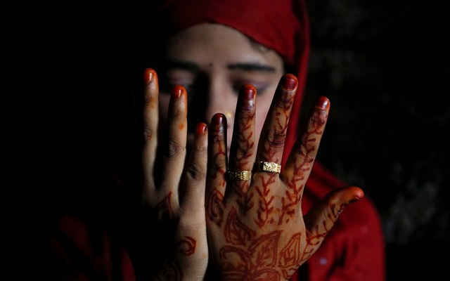 Shofika Begum, 18, shows decoration on her hands on the day she marries Saddam Hussein, 23, both Rohingya refugees, at the Kutupalong camp near Cox's Bazar, Bangladesh, December 11, 2017. Reuters