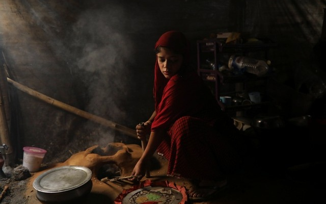 Shofika cooks inside their temporary shelter days after the wedding. Reuters