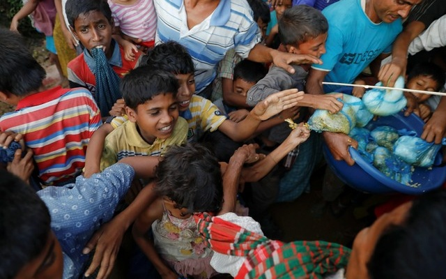 Refugee children scuffle over free meals given away during the wedding party. Reuters