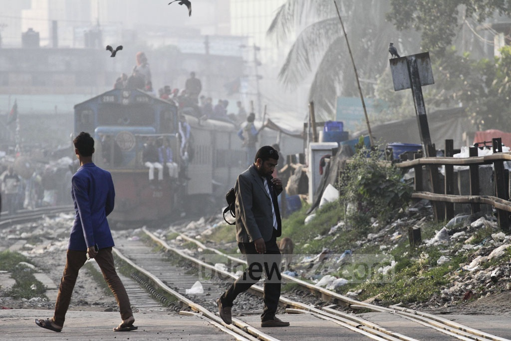 Pedestrians in Dhaka risk crossing the rail tracks as a train approaches the level-crossing. Photo taken on Monday at the city's Karwan Bazar. Photo: dipu malakar