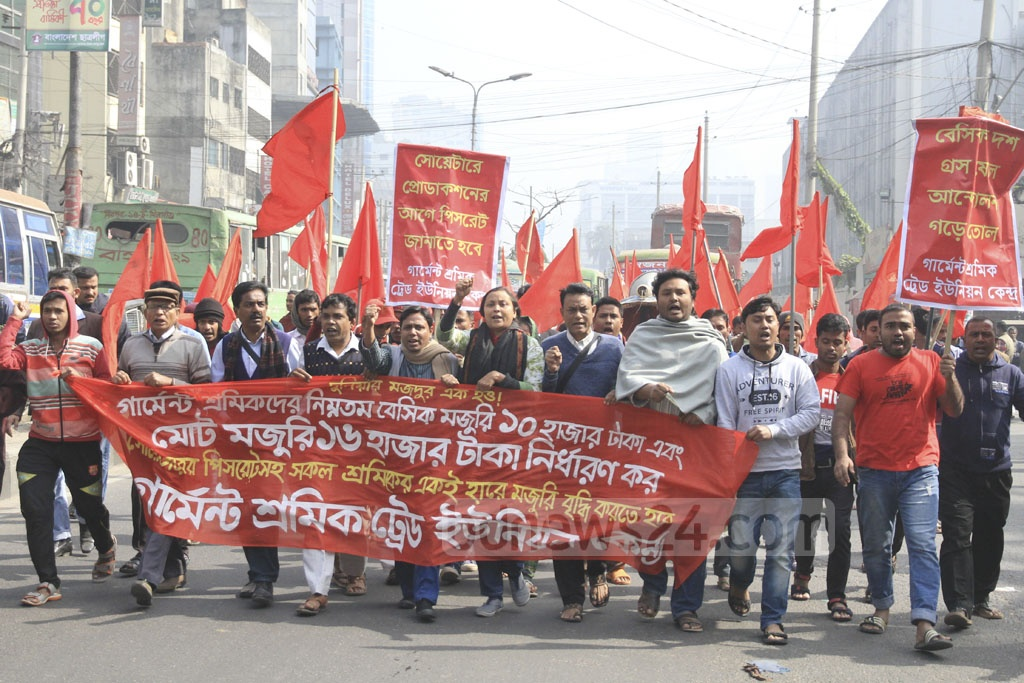Garment trade union members and leaders march in front of the National Press Club on Monday to demand a minimum wage of Tk 10,000.