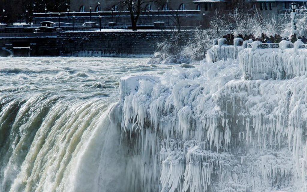 Visitors take pictures near the brink of the ice covered Horseshoe Falls in Niagara Falls, Ontario, Canada, January 3, 2018. Reuters