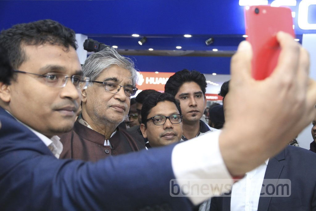 Posts, Telecommunications and IT Minister Mustafa Jabbar (second from right) smiles with others as State Minister Zunaid Ahmed Palak takes a group selfie as they go around stalls after inauguration of the three-day-long 'Smartphone and Tab Expo 2018' on Thursday. Photo: Abdullah Al Momin