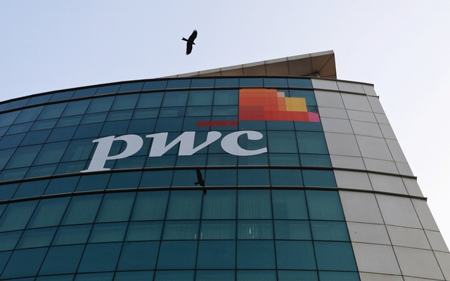 A bird flies past the logo of Price Waterhouse installed on the facade of its office in Mumbai, India, Jan 11, 2018. Reuters i