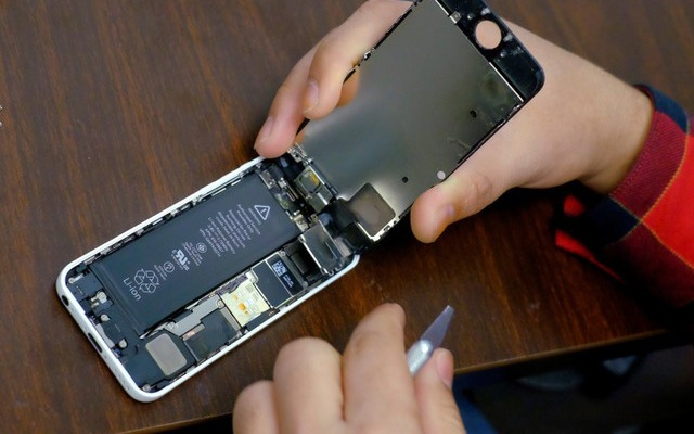 FILE PHOTO: A battery is exposed as a man tries to repair an iPhone in a repair store in New York, February 17, 2016. Reuters