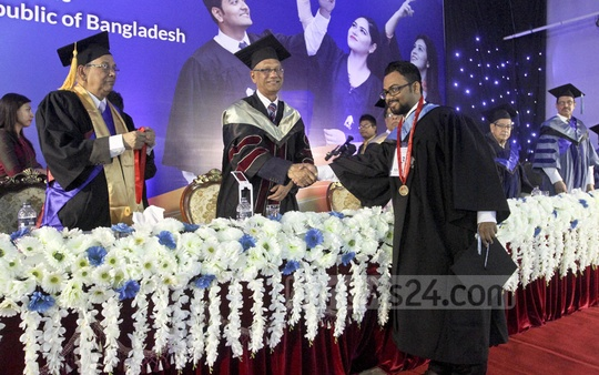 Education Minister Nurul Islam Nahid confers a medal on a student of East West University at its 17th Convocation on Thursday. Photo: dipu malakar