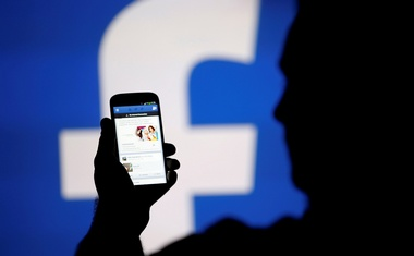 File Photo: A man is silhouetted against a video screen with a Facebook logo as he poses with an Samsung S4 smartphone in this photo illustration Aug 14, 2013. Reuters
