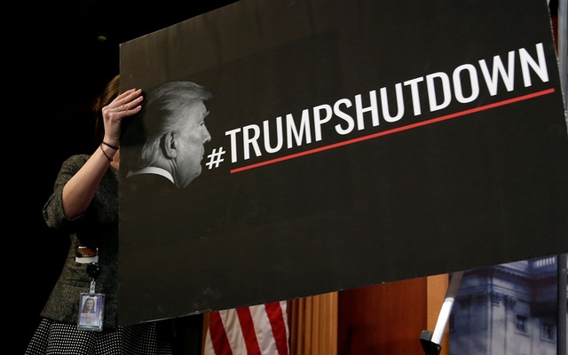 A Senate staffer places a sign blaming US President Donald Trump for shutdown of the Federal Government before a news conference with Senate Minority Leader Chuck Schumer (D-NY) on Capitol Hill in Washington, US, Jan 20, 2018. Reuters