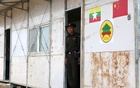 A Myanmar immigration official stands at the door of a building inside the camp set up by Myanmar's Social Welfare, Relief and Resettlement Minister to prepare for the repatriation of displaced Rohingyas, who fled to Bangladesh, outside Maungdaw in the state of Rakhine, Myanmar Jan 24, 2018. Reuters