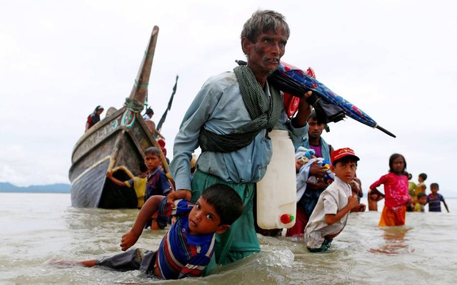 A Rohingya refugee man pulls a child as they walk to the shore after crossing the Bangladesh-Myanmar border by boat through the Bay of Bengal in Shah Porir Dwip, Bangladesh, Sept 10, 2017. Reuters