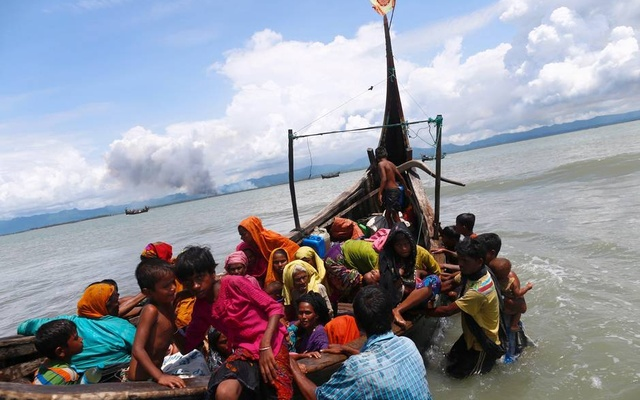 Smoke is seen on Myanmar's side of border as Rohingya refugees get off a boat after crossing the Bangladesh-Myanmar border through the Bay of Bengal in Shah Porir Dwip, Bangladesh September 11, 2017. Reuters