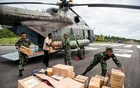 Indonesian soldiers along with a local resident unload food and medical aid in Ewer, Asmat District, in the remote region of Papua, Indonesia January 29, 2018 in this photo taken by Antara Foto. Picture taken January 29, 2018. Antara Foto/M Agung Rajasa/ via REUTERS