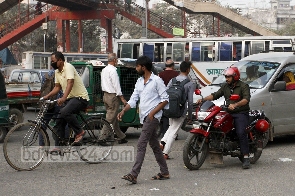 Pedestrians risk crossing a busy street in Dhaka despite of a foot over-bridge. Photo taken on Monday at the capital's Mirpur-10 intersection. Photo: asif mahmud ove